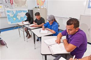 Two male and two female students sitting in a High School Equivalency class while participating in the class assignment.