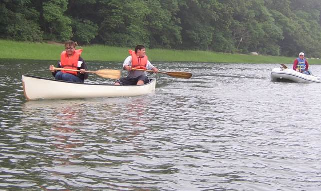 Students canoe with zodiac patrolling