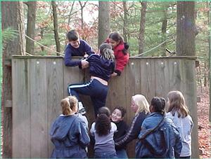 Students helping another student climb a wooden fence.
