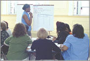 Instructor standing in front of class holding a microphone while providing data analysis training.