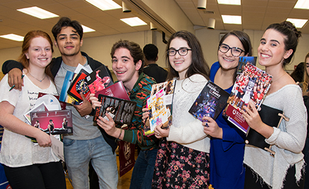 A group of six high school students hold up brochures they collected during the school's college night event