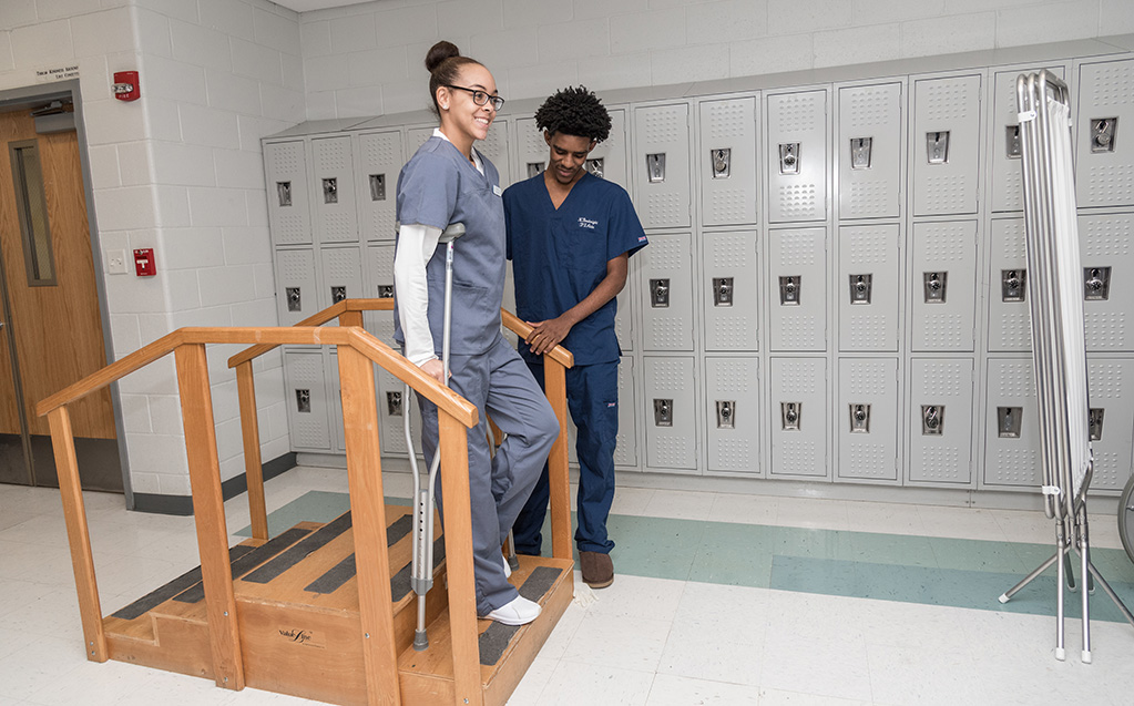 Student practices helping a rehabbing person walk up and down the stairs.