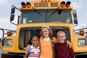 three happy students standing in front of a School Bus
