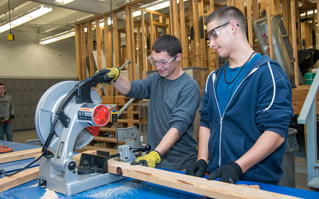 Two students use a miter saw to cut a 2x4 for their project.