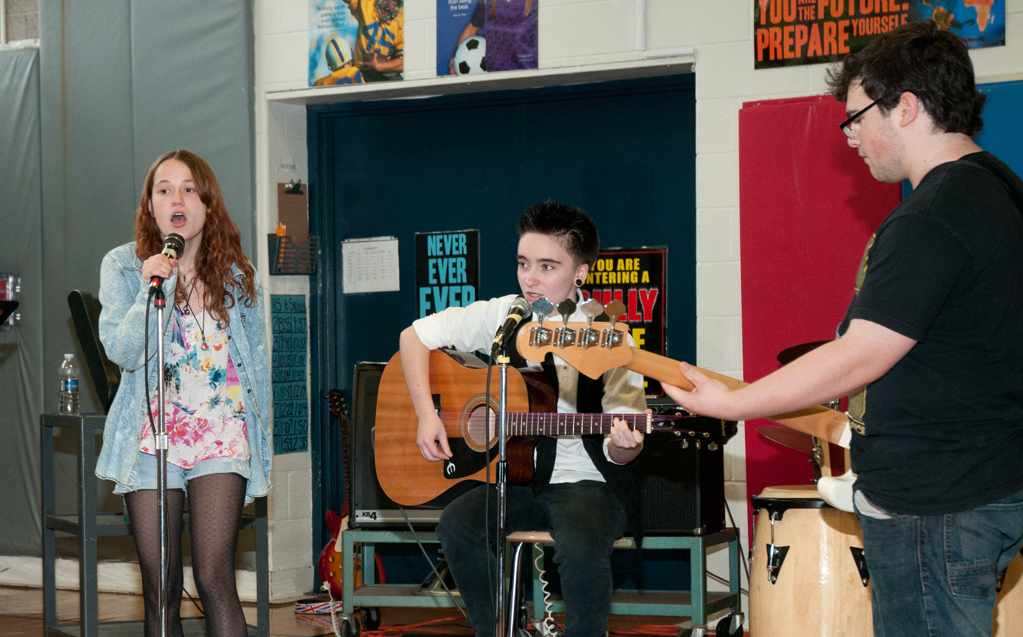 Three students performing in class. A female vocalist accompanied by a male acoustic guitar player and another male playing an electric bass guitar.