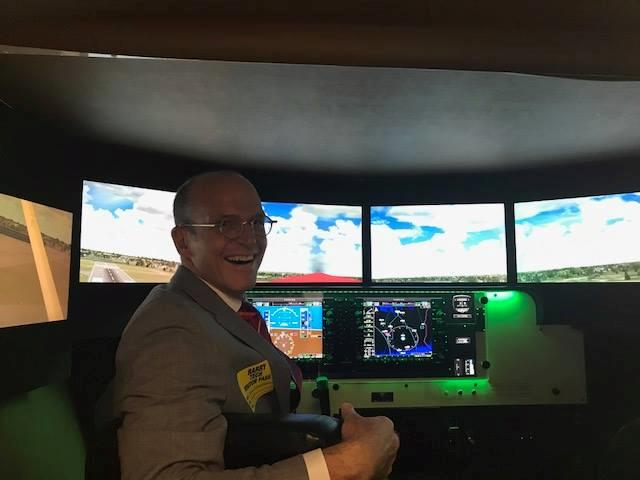 Smiling man in suit sits in flight simulator