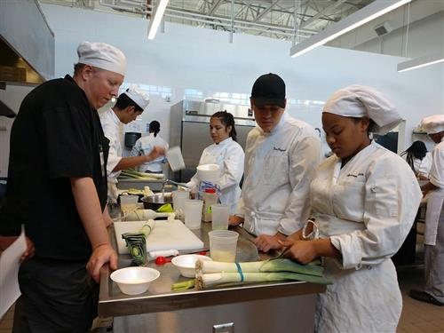 Chef teacher looks on as students prepare ingredients in kitchen