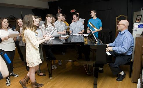 Students sing around piano