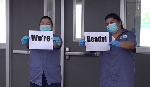 "Custodians hold up ""We're Ready"" signs"