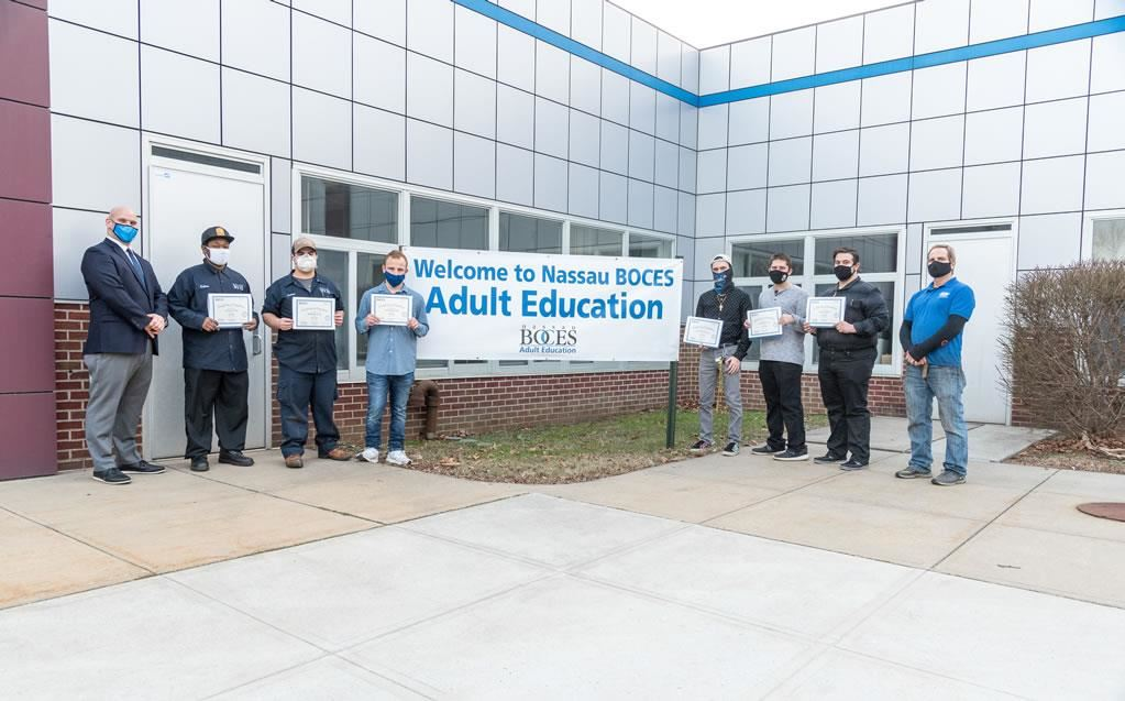 Students from the Auto Lube course display certificates of completion of the ISP