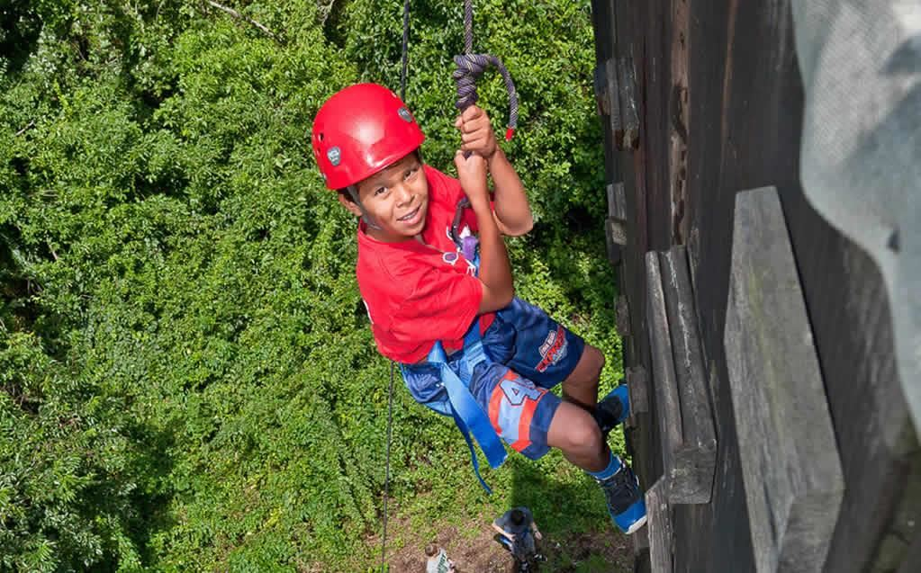 A student scales the climbing wall as part of the Outdoor Education Adventure Challenge course.