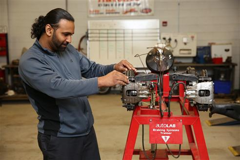 Auto Mechanics students tinkers with a small engine