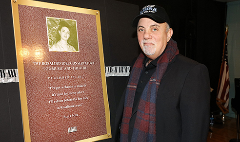 Billy Joel stands with plaque honoring his mom