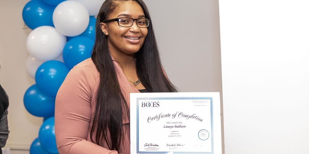 Lanaya Baldwin proudly displays her certificate of completion from the ISP program at Nassau BOCES A