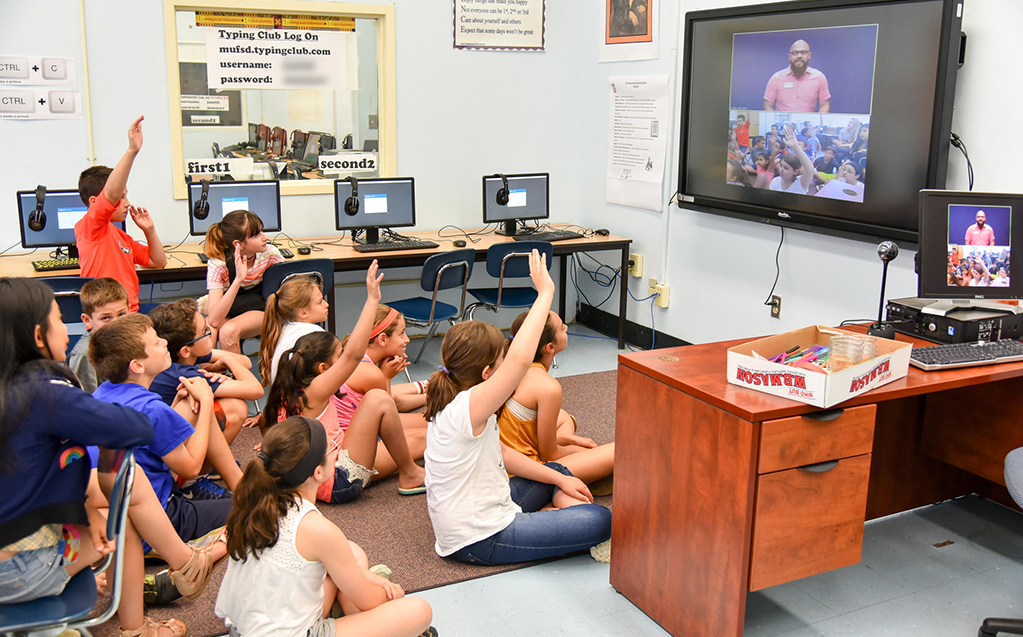 Eager young students participate in a classroom lesson with a remote educator through videoconferencing technology