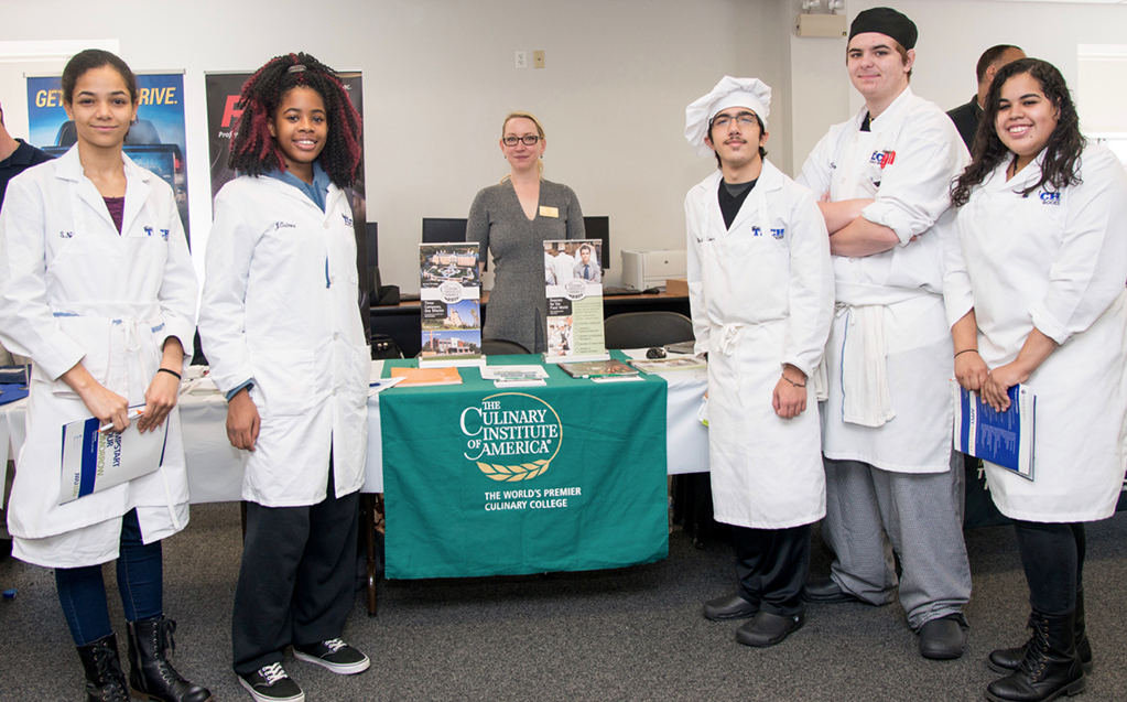 Culinary students pose with representative from The Culinary Institute of America